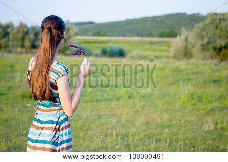 Woman on summer meadow with flowers at sunset