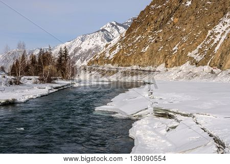 Scenic spring view on the fast mountain river flowing among the shores of ice and snow on background of mountains trees and blue sky