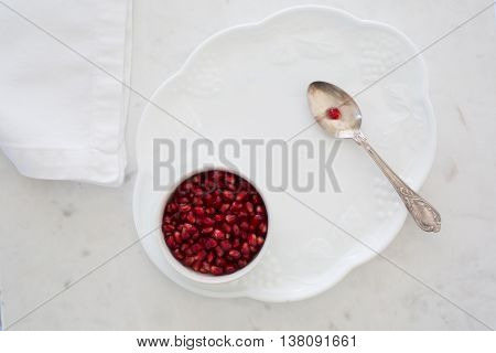 Top-down view of pomegranate seeds in a small bowl set on a dessert plate on white marble with napkin and silver sppon. One aril (seed) on spoon.