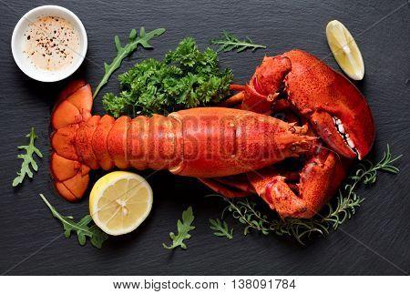 Whole boiled lobster on black slate plate