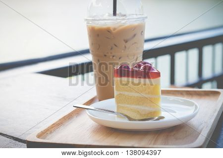 Sponge cherry cake with cherry syrup. Peace of cherry cake serve with iced coffee. Cherry cake in cozy outdoor cafe.