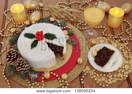 Christmas cake and slice, with egg nog, holly berries, candles, noel glitter sign, gold bauble decorations and foil wrapped chocolates with bead strands over oak table background.