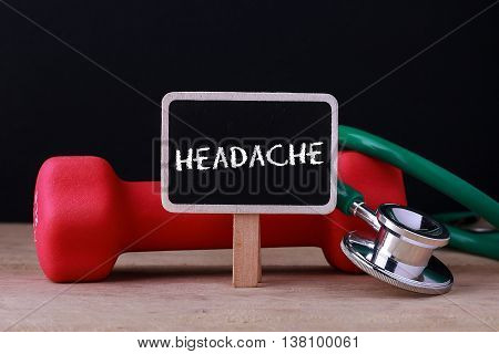 Medical concept - Stethoscope and dumbbell on wood with Headache word