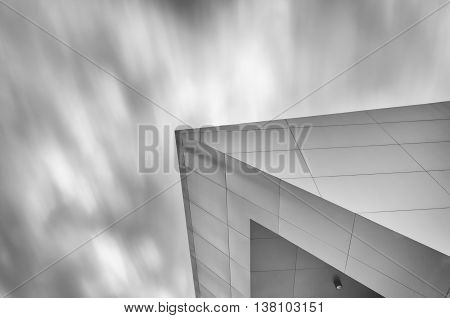 The conner of a giant building in the sky and motion cloud moving