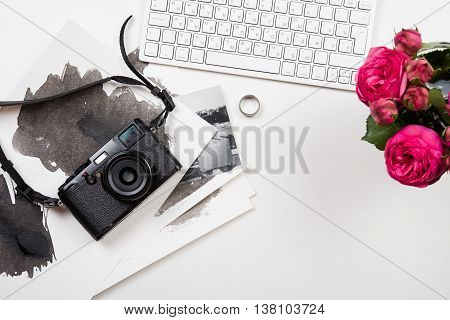 Modern computer keyboard, pink flowers and photo camera on white table, photographer girl's workspace