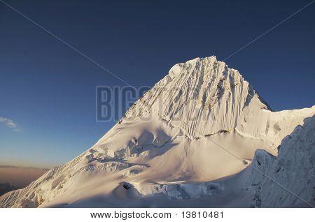 Peak Alpamayo on the sunset in Cordilleras
