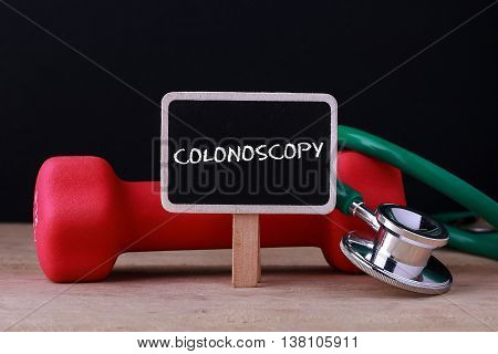 Medical concept - Stethoscope and dumbbell on wood with Colonoscopy words