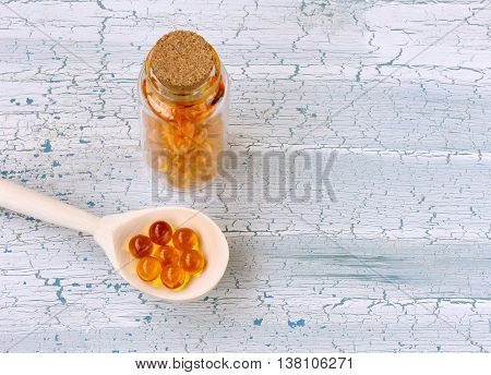 cod liver oil capsules in wooden spoon medical vial on wooden table