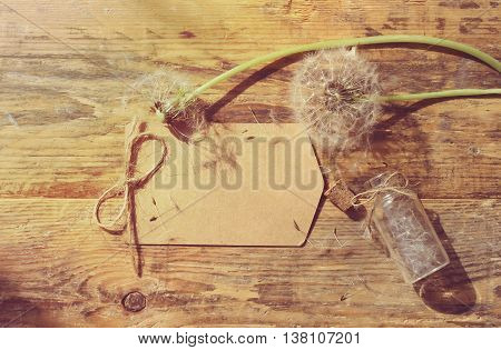 Summer background with dandelion on wooden table small bottle with seeds paper label retro rustic style