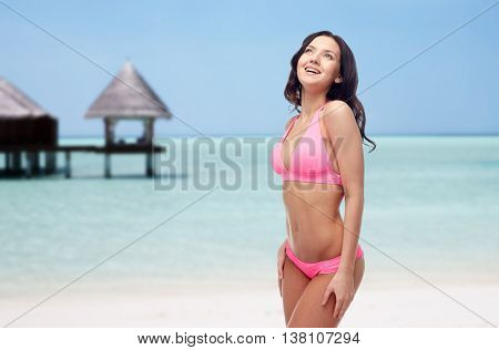 people, travel, tourism, swimwear and summer holidays concept - happy young woman in pink bikini swimsuit over exotic tropical beach with bungalow in sea background
