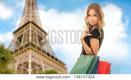people, holidays, tourism, travel and sale concept - young happy woman with shopping bags over paris eiffel tower background