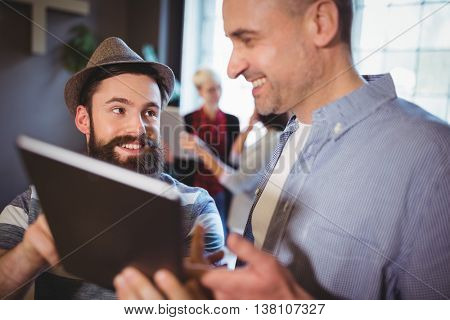 Happy male colleagues discussing over digital tablet in creative office