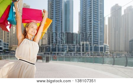 people, holidays, tourism, travel and sale concept - young happy woman with shopping bags over dubai city street background
