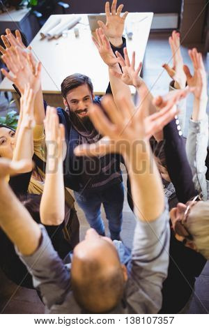 High angle view of creative business people cheering in office