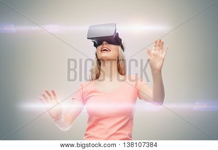 technology, virtual reality, entertainment and people concept - happy young woman with virtual reality headset or 3d glasses over gray background and laser light