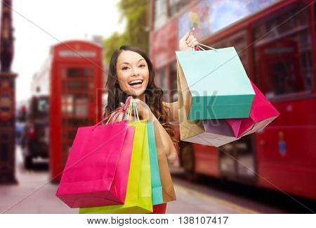 people, holidays, tourism, travel and sale concept - young happy woman with shopping bags over london city street background