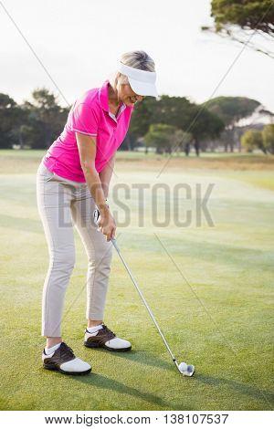 Woman golfer preparing her shot on a field