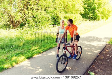 fitness, sport, summer, people and healthy lifestyle concept - happy couple with rollerblades and bicycle riding and talking outdoors at summer