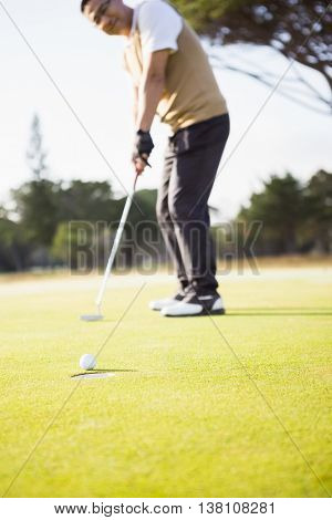Focus on foreground of golf ball and a hole on a field