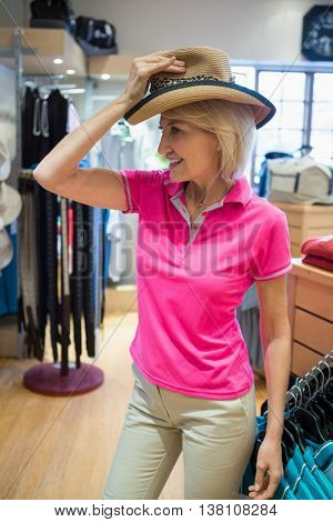 Mature woman trying on a hat in a store