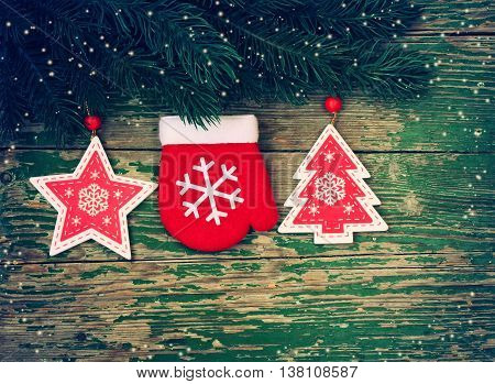 Christmas background with branch spruce decoration mittens star and fir tree on wooden table retro style