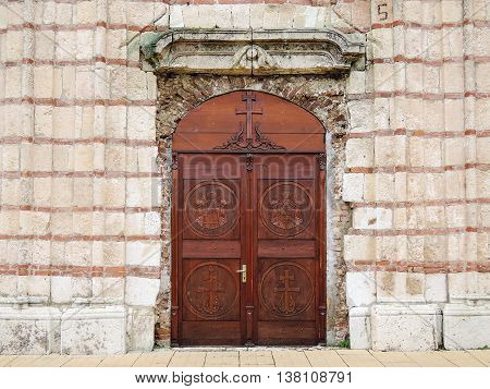 Church door. Entrance wooden door of the old Orthodox Church decorated with carvings on the background of stone facade wall.