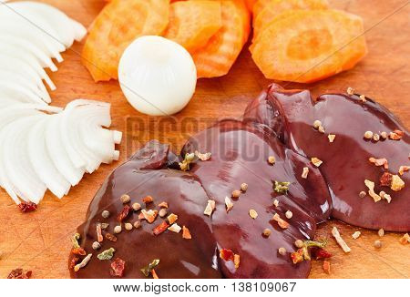 Fresh raw chicken liver with spices on wooden background. Cooking food.