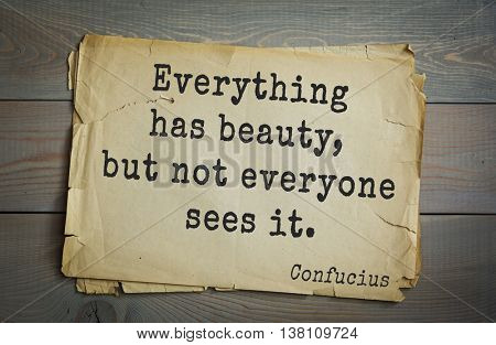 Ancient chinese philosopher Confucius quote on old paper background.  Everything has beauty, but not everyone sees it.