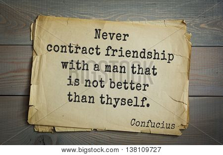 Ancient chinese philosopher Confucius quote on old paper background. Never contract friendship with a man that is not better than thyself.