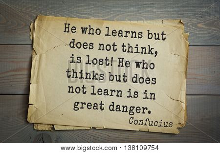 Ancient chinese philosopher Confucius quote on old paper background.  He who learns but does not think, is lost! He who thinks but does not learn is in great danger.