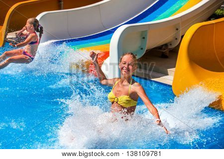 Two children on water slide at aquapark and thumb up. Summer holiday. There are two water slides in aqua park. Outdoor. Water children holiday.
