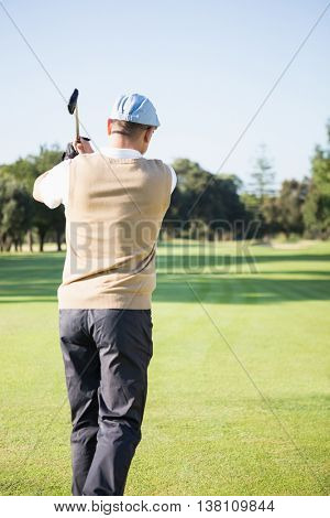 Rear view of sportswoman playing golf on field
