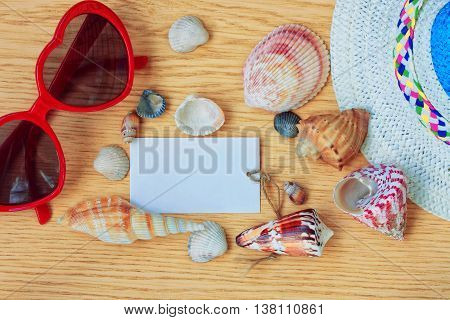 summer straw hat sun glasses and seashells on a wooden table vacation concept paper label