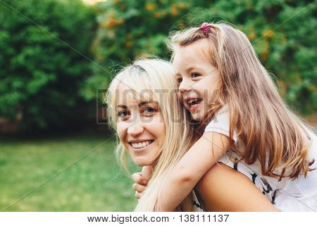 Family relaxing on green grass in the backyard. Child with mom.