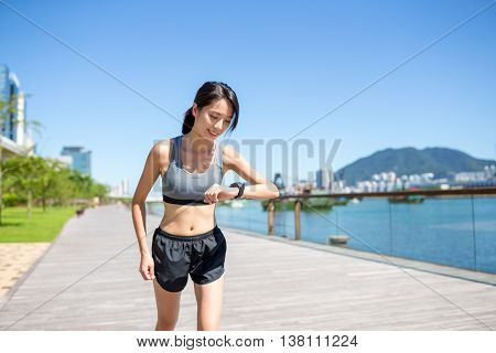 Woman running at morning and checking the record on smart watch
