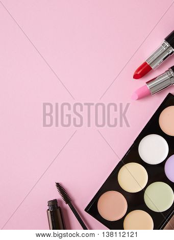 A selection of make up products laid out on a pink background forming a page border
