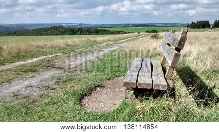Bench for hikers and wanderers on green meadow