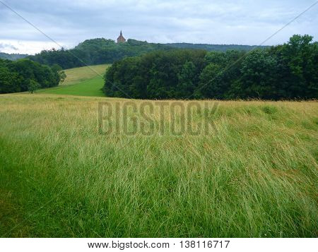 Landscape With Green Meadow And A Church On A Hill