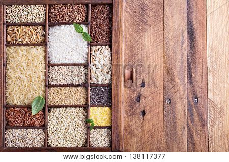 Variety of healthy grains and seeds in a wooden box mostly gluten free with rice, quinoa and buckwheat