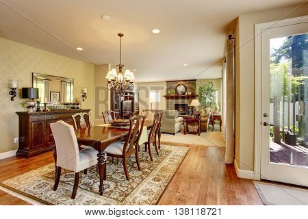 Classic American Dining Room With Wooden Table Set, Hardwood Floor And Rug.