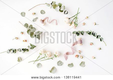 empty wreath frame with roses eucalyptus branches leaves and spool with ribbon isolated on white background. flat lay overhead view