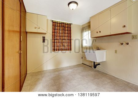 Laundry Room With Beige Walls And Tile Floor. Furnished With Cabinets And Built-in Wardrobe