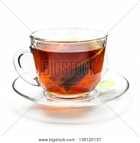 Transparent cup of black tea with tea bag isolated on white background
