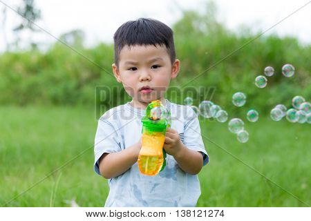 Little boy play with bubble blower at outdoor