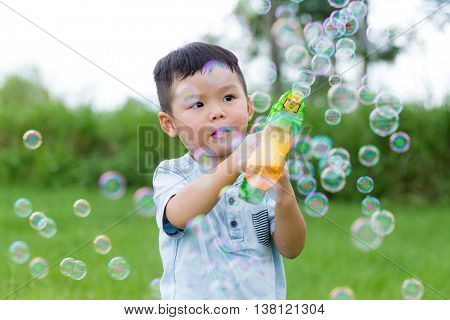 Little child play with bubble blower gun