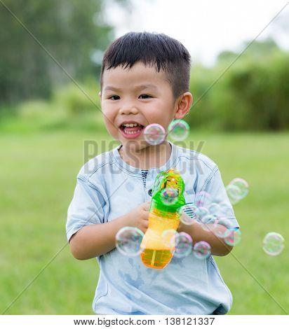 Asian little boy play with bubble blower gun