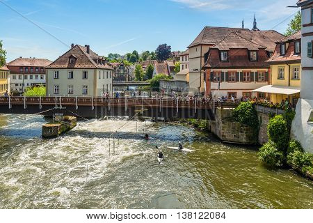 Bamberg Germany - May 22 2016: Tourists on a bridge and canoe slalom on the River Regnitz Bamberg Bavaria Germany Europe. The historic city center of Bamberg is a listed UNESCO world heritage site.
