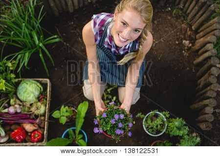 Portrait of happy young gardener with potted plant at botanical garden