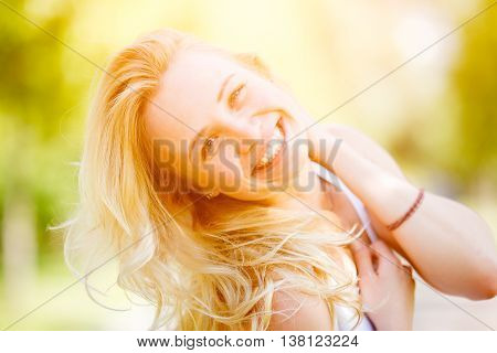 Blonde woman threw back her head. Image with lens flare effect