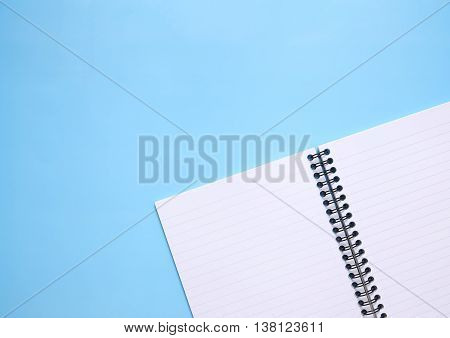 A lined, sprial bound notebook open on a blank page on a blue background forming a page border